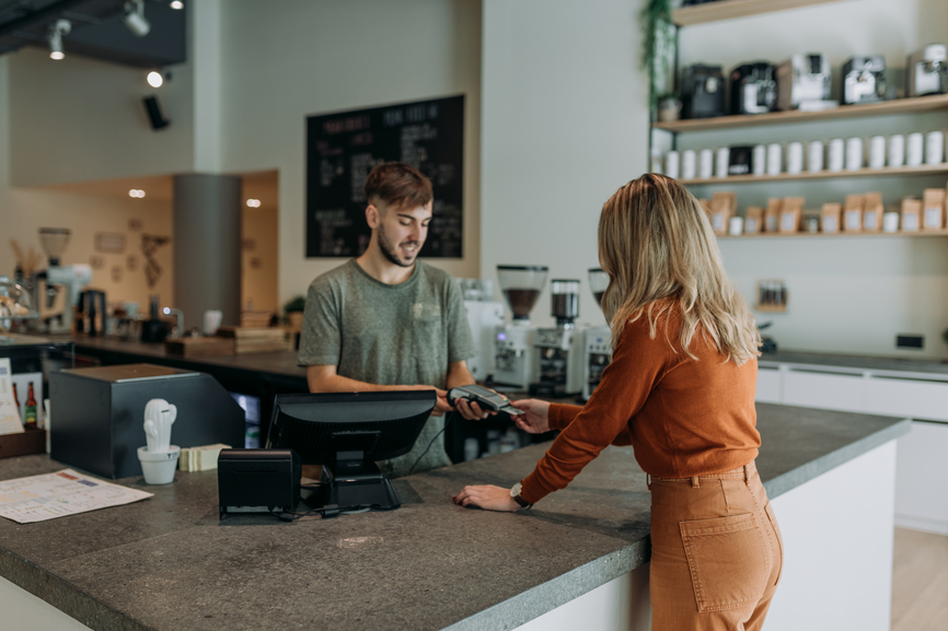 blonde woman paying in a cafe